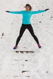 Young girl jumping on the snow. Royalty Free Stock Photo