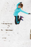 Young girl jumping on the snow. Royalty Free Stock Images
