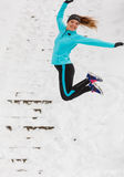 Young girl jumping in the snow. Royalty Free Stock Photos