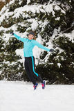 Young girl jumping in the snow. Stock Photo