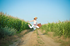 Young girl jumping with suitcase on road in corn Stock Photography