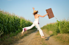 Young girl jumping with suitcase on road in corn Stock Photo