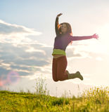 Young girl jumping in the sunset light.  Royalty Free Stock Photography