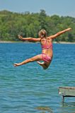 Young Girl Jumps Off Dock Stock Photography