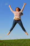 Young girl jumps and screams at grass stock photo