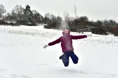 Young girl jumps up in height from joy in the snow stock photo