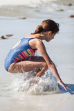 Young girl jumps in the water at the beach Royalty Free Stock Photography