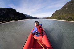 Young girl kayaking down a dart river of New Zealand. Girl traveling down river stream. Woman enjoying scenery. Lifestyle, adventure and exploration concept stock photography