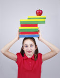 Young girl keeps books and apple on his head. Young girl keeps a lot of books and an apple on his head Stock Image