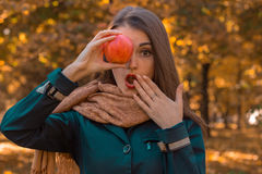 Young girl keeps one hand near the mouth and in the other   Apple  eyes closeup Stock Photo
