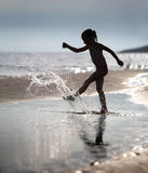 Young girl kicks the water at the beach holiday. Silhouette of a slim, little girl, who plays at the beach Royalty Free Stock Photography