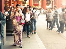Young girl with kimono holding a mobile phone at Senso-ji Temple Stock Photos