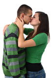 Young girl kisses and hugs her boyfriend isolated Stock Photography