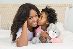 Young girl kissing her smiling mother on bed Stock Photo