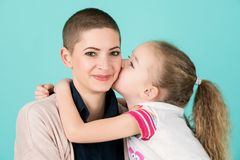 Young girl kissing mother, young cancer patient, on the cheek. Cancer and family support. Young girl kissing mother, young cancer patient, on the cheek. Cancer royalty free stock photos