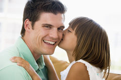 Young girl kissing smiling man in living room Royalty Free Stock Image