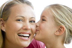 Young girl kissing smiling woman. Close up of a young girl kissing smiling woman Stock Photos