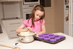 A young girl in the kitchen baking cupcakes Stock Photo