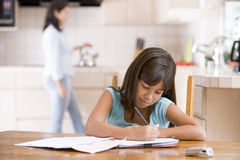 Young girl in kitchen doing homework with woman in Stock Photo