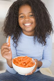 Young girl in kitchen eating carrot sticks smiling Stock Photo