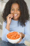 Young girl in kitchen eating carrot sticks smiling Royalty Free Stock Image