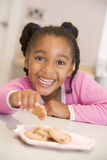 Young girl in kitchen eating cookies smiling Royalty Free Stock Photography