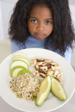 Young girl in kitchen eating rice fruit and nuts Royalty Free Stock Image