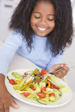 Young girl in kitchen eating salad smiling Stock Image