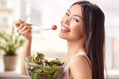 Young girl at kitchen healthy lifestyle standing with bowl eating salad looking camera cheerful royalty free stock photo