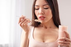 Young girl at kitchen healthy lifestyle standing holding milkshake looking at spoon thoughtful close-up royalty free stock images