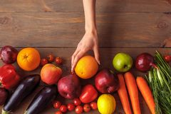 Young girl at kitchen healthy lifestyle table close-up taking orange from other products stock photos