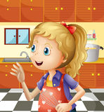 A young girl at the kitchen holding a mixer Stock Photo