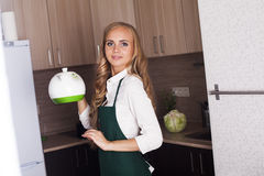 Young girl in the kitchen kettle Stock Images