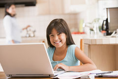 Young girl in kitchen with laptop and paperwork Royalty Free Stock Photos