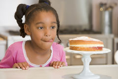 Young girl in kitchen looking at cake on counter Stock Photo