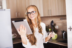 Young girl in the kitchen looking for a recipe on Stock Image