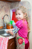 Young girl in the kitchen washing dishes Stock Photos