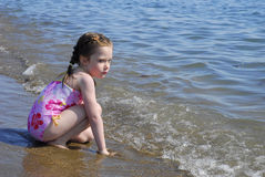 Young Girl kneels in the surf on a beach. Royalty Free Stock Photography