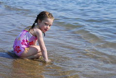 Young Girl kneels in the surf on a beach. Royalty Free Stock Photo