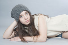 Young girl in a knitted hat lying on the floor. Royalty Free Stock Photography