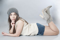 Young girl in a knitted hat lying on the floor. Royalty Free Stock Photo