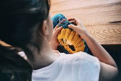 Young girl knitting a circle scarf. Learnig knitting basics. stock photography