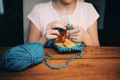 Young girl knitting a circle scarf. Learnig knitting basics. stock photos