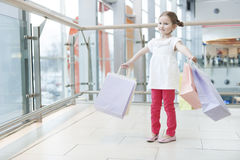 Young girl laden with paper shopping bags Stock Photos