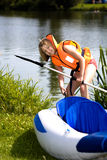Young girl at a lake. Young girl in a lifejacket pulling an inflatable boat to the lake Stock Photography