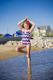 Young girl at the lake in yoga pose Stock Image