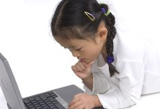 Young girl on a laptop. A young girl laying on the floor playing with a laptop stock photo