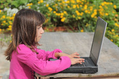 Young girl with laptop. Young girl with notebook is exercised in the garden Stock Photography