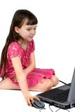 Young Girl On a Laptop. A cute young girl in a pink dress enjoys learning how to use a laptop computer Stock Image