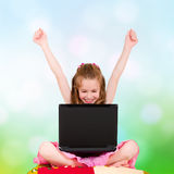 A young girl with a laptop. Sitting and have joyfully hands up stock photos